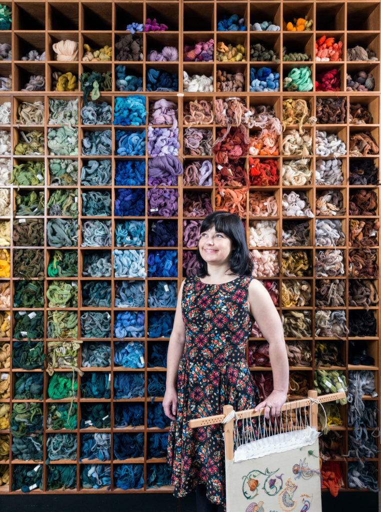 Kate Barlow, In front of the 'Wall of Wool', Royal School of Needlework. Kate is a current Future Tutors student at the Royal School of Needlework. Founded in 1872 and based in Hampton Court Palace, the Royal School of Needlework is the international centre of excellence for the art of hand embroidery. © Historic England/Chris Redgrave