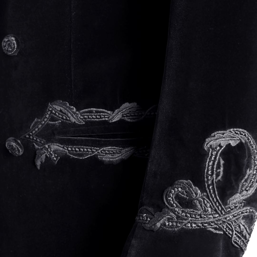 Double breasted black velvet smoking jacket with silk satin shawl collar lapel. Embroidered design around pocket jettings and on sleeves.