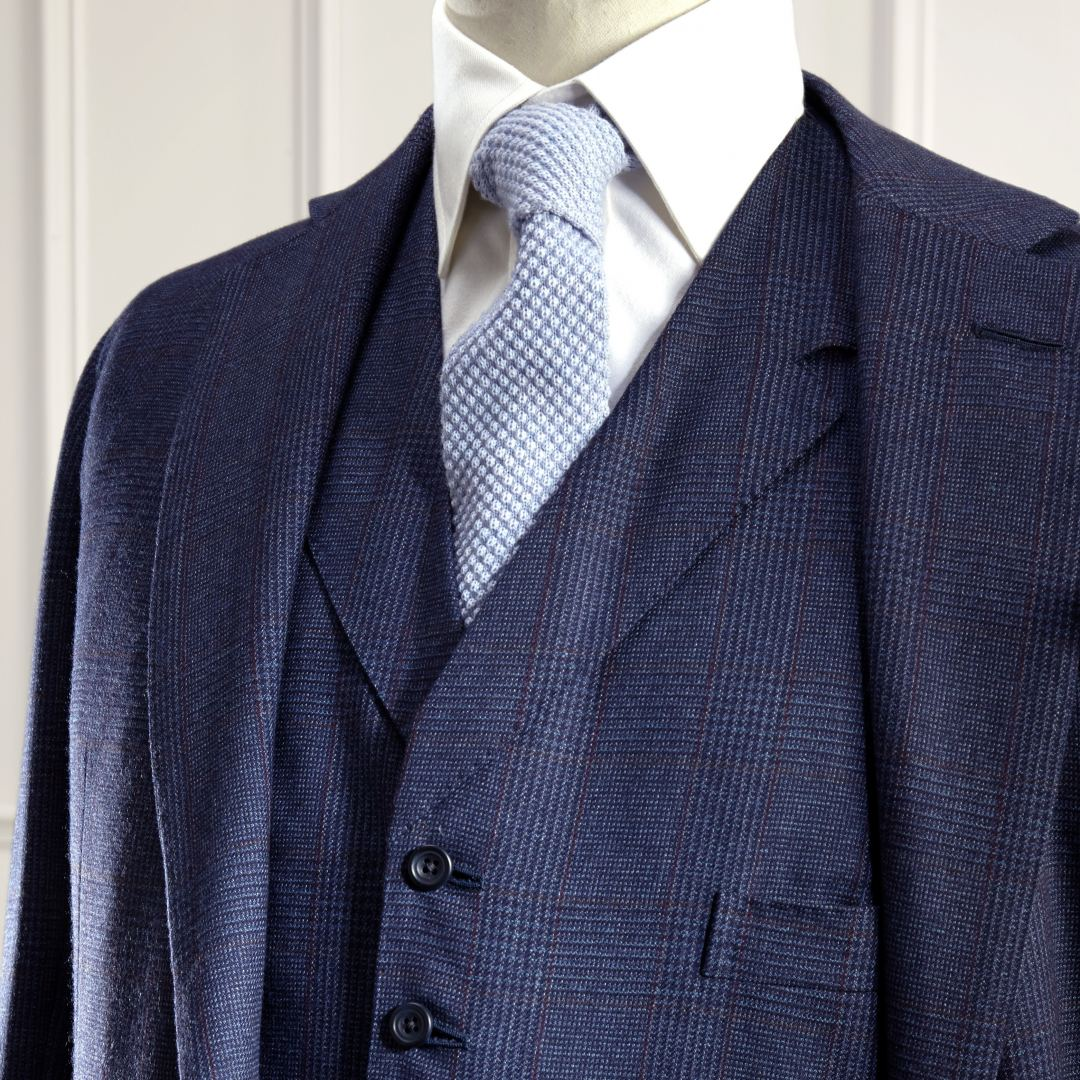 Single breasted three piece suit in dark blue and red glen check. The jacket features two side vents, flaps, two in breast ticket pockets, an out ticket pocket on the right hand side and horn buttons. Cloth made exclusively for Anderson & Sheppard in Scotland.