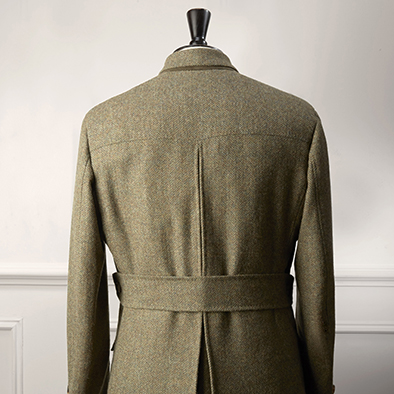 Double breasted loden green herringbone field jacket. The jacket features two welted pockets, two bellowed pockets with centre pleat, half belt and centre pleat at back, quilted lining and horn buttons.