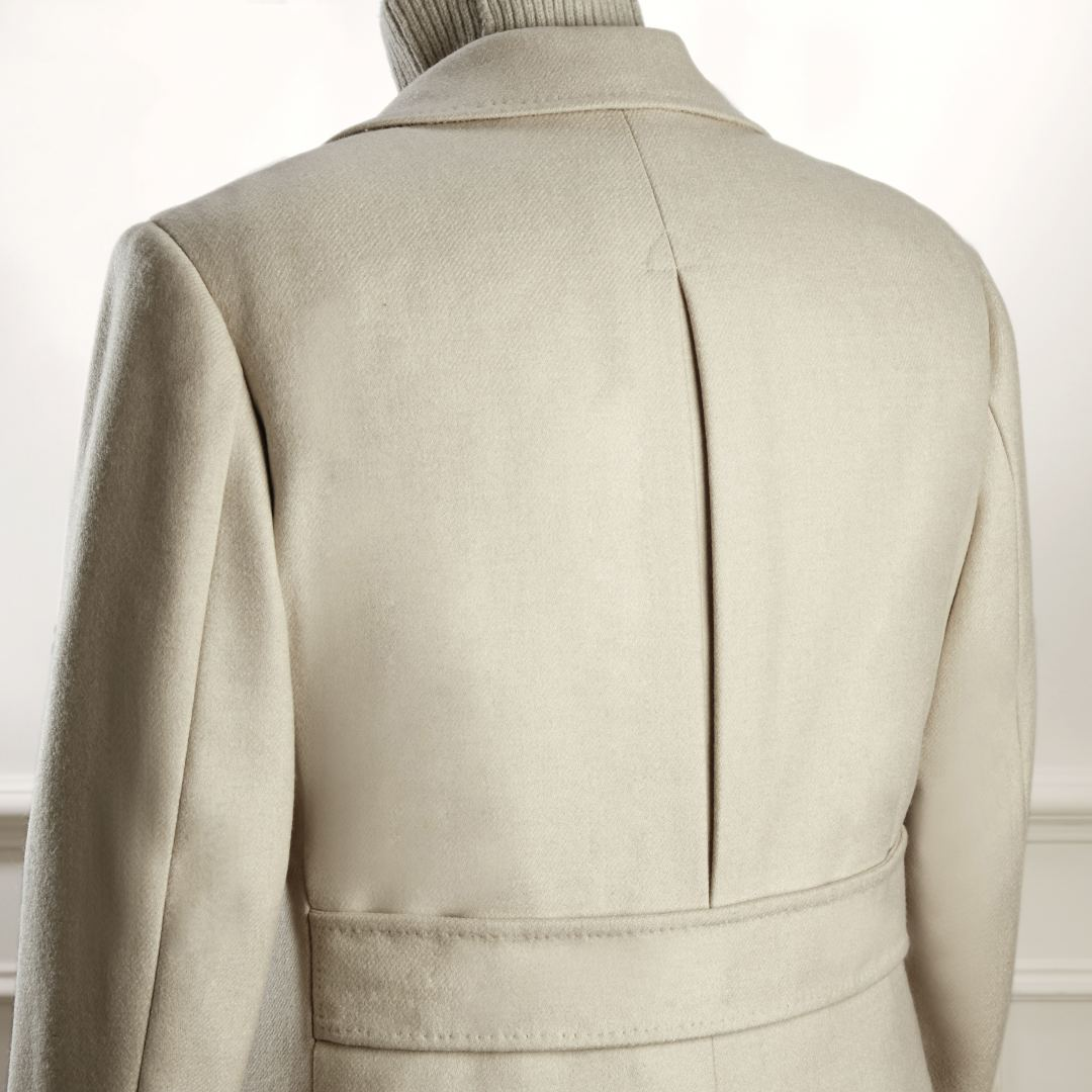 Double breasted oatmeal serge overcoat with slanted welted pockets, two in-breast pockets, slit at back, half belt and quilted lining.
