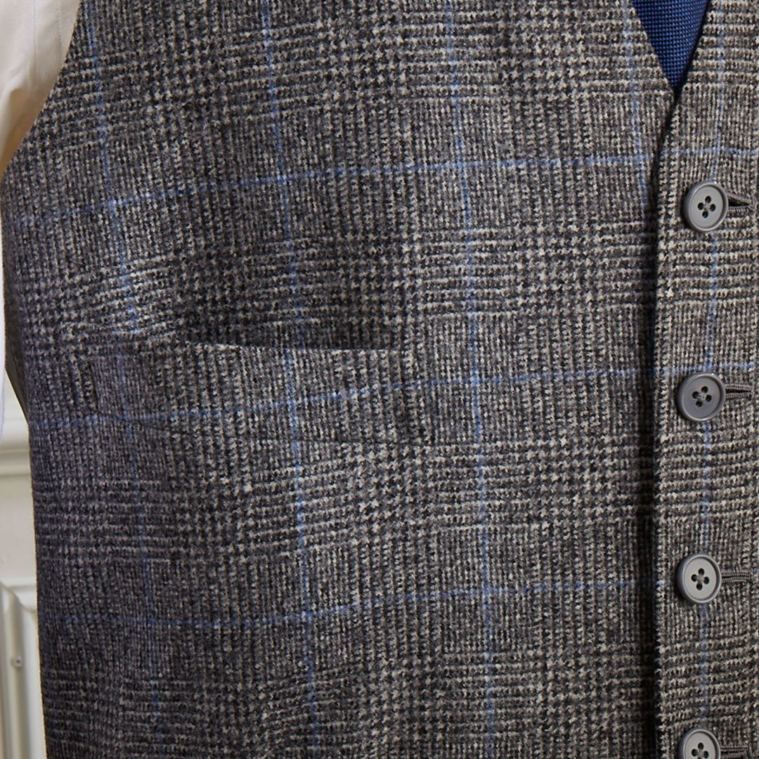 Single breasted flannel three piece suit in medium grey Prince of Wales check with blue overcheck. Three button roll through lapel and jetted pockets with flaps.