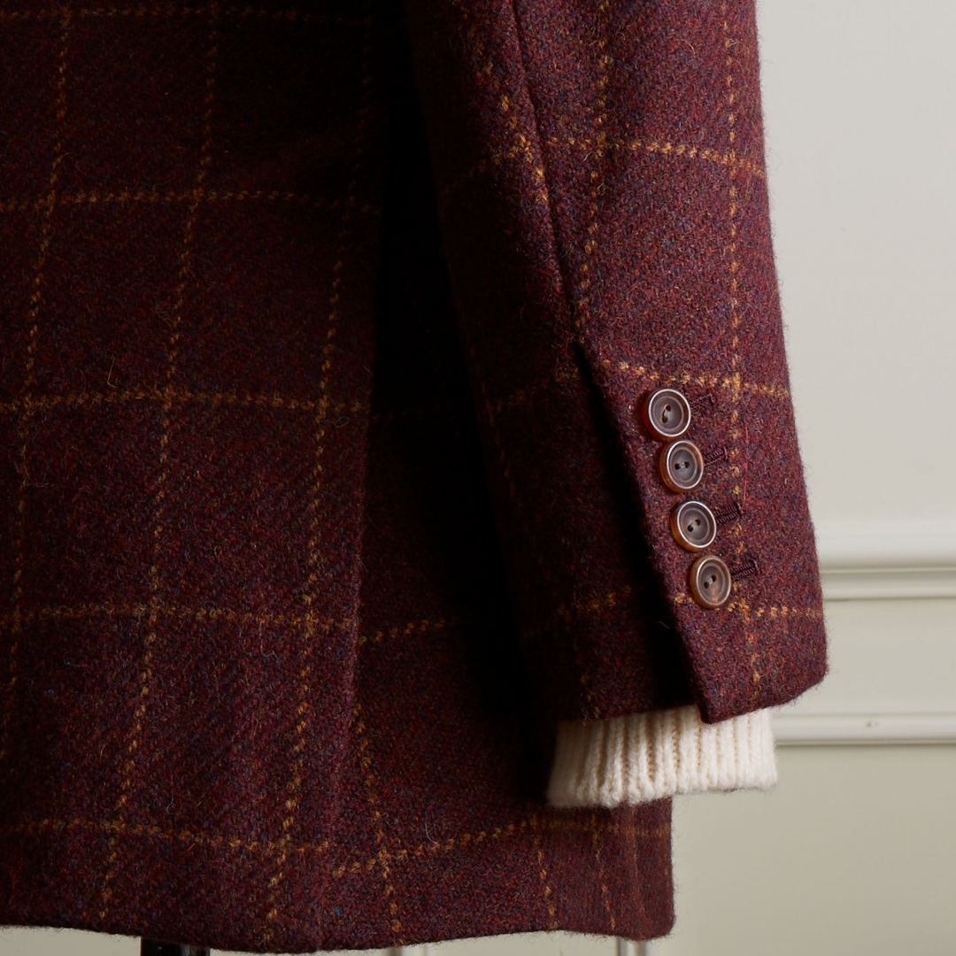 Single breasted jacket with notch lapel made from one of Anderson & Sheppard exclusive'Special' burgundy tweeds with gold over check. Pockets with flaps, out ticket pocket and horn buttons.