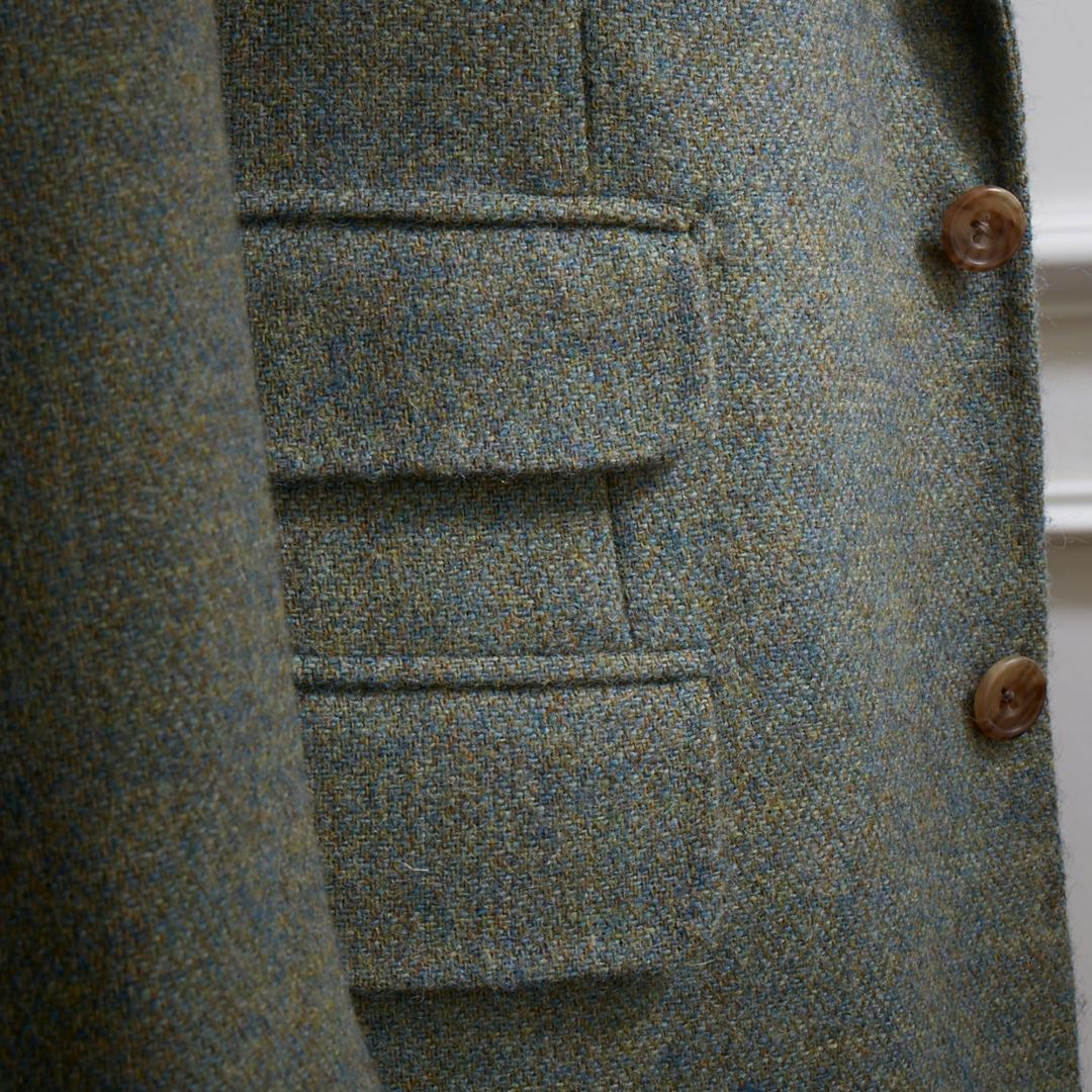 Single breasted jacket in green Shetland 12 / 13 oz tweed with a three button roll through lapel. Pockets with flaps, horn buttons and swelled edge stitching.