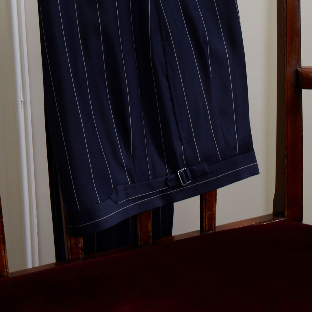 Double breasted jacket in lightweight navy pinstripe cloth with jetted pocket and flaps. Pleated trousers with side adjuster tabs.