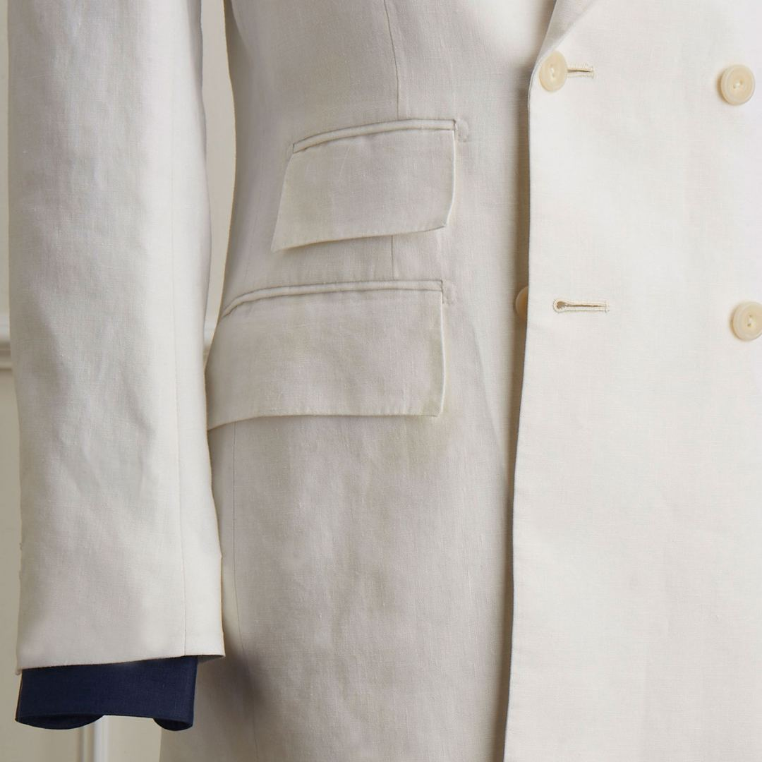 Double breasted jacket in white Irish linen. Jetted pockets with flaps, out ticket pocket and horn buttons.